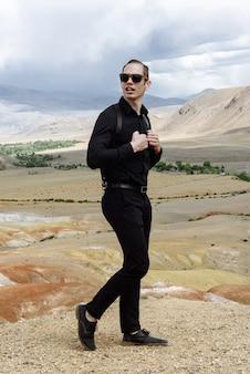사막 산을 배경으로 포즈를 취하는 선글라스와 검은 옷을 입은 남자 모델