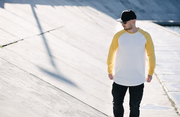 Модель-мужчина с бородой в бело-желтой пустой рубашке с длинным рукавом для макета и бейсболке с местом для вашего логотипа или дизайна в повседневном городском стиле