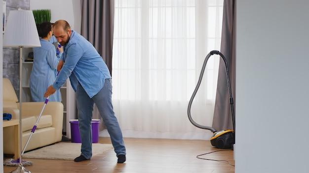 남자는 바닥을 청소하고 아내는 가구의 먼지를 청소