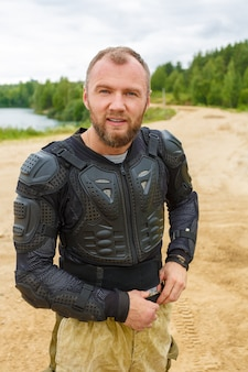 Man in motorcycle suit dressing up.