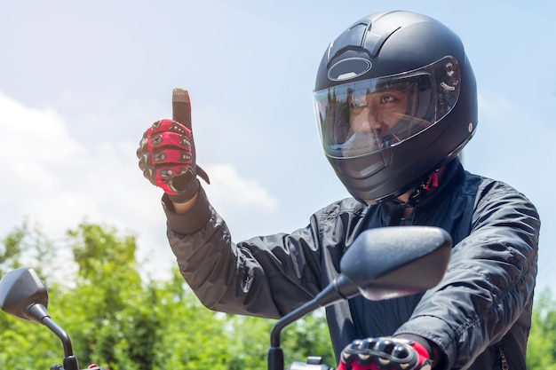 Man in a motorcycle with helmet and gloves is protective clothing for motorcycling