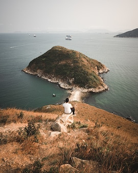Uomo sul monte johnston, hong kong, guardando l'acqua