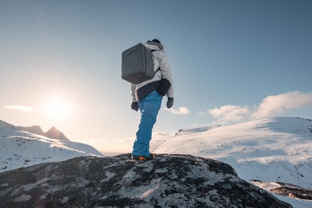 Человек альпинист, стоя на скале с солнцем на холме снег