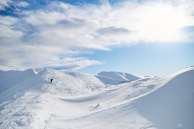 Альпинист человек идет на холм, покрытый свежим снегом. карпаты