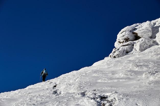 언덕에 걷는 남자 산악인은 신선한 눈으로 덮여 있습니다. 카르 파티 아 산맥