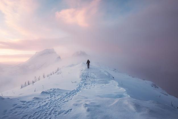 Альпинист человека идет с следом на снежной горе и красочном небе в метель на восходе солнца.