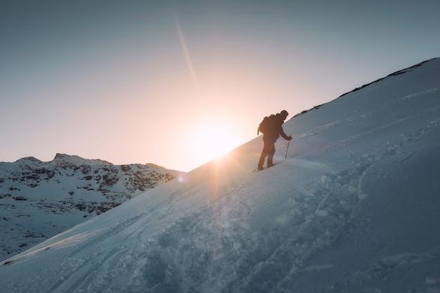Человек-альпинист с треккинговым шестом, восхождение на заснеженный холм и солнце на горе райтен, лофотенские острова