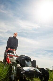 Мужчина косит, косит траву на своем огромном садовом дворе, зеленое поле у моторной садовой косилки, концепция садоводства