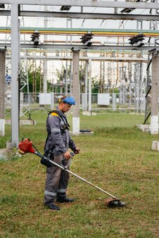 Man mowing grass on the territory of an electric substation in overalls