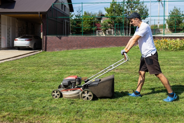 Man mowing the lawn in the backyard
