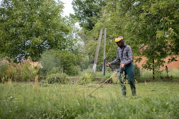 그의 정원에서 잔디를 깎고 남자