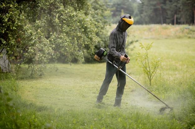 그의 정원에서 잔디를 깎고 남자.