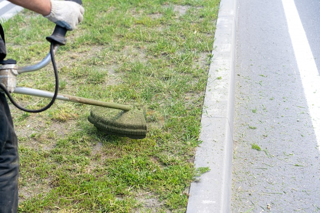 Man mows the grass with a lawn mower