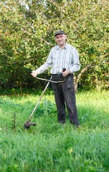 남자는 정원에서 잔디를 깎고 프리미엄 사진