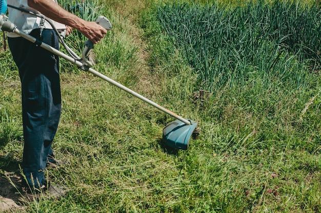 남자는 잔디 깎는 기계로 잔디를 깎습니다. 가솔린 잔디 깎는 기계, 잔디 트리머. 남자는 정원에서 일한다