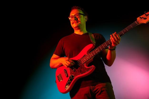 Man musician playing guitar on neon light