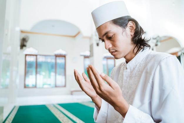 Мужчина-мусульманин молится в мечети