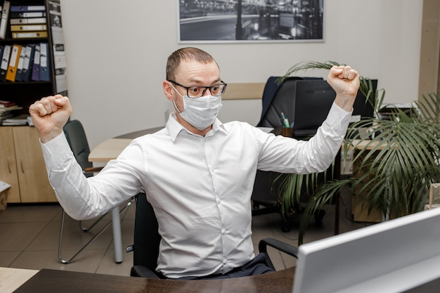 Man n protective mask looking at laptop excited by good coronovirus news