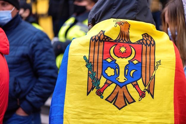 Uomo con bandiera nazionale e persone che protestano per le elezioni anticipate di fronte all'edificio della corte costituzionale
