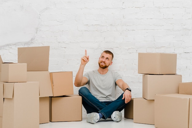 Man near boxes pointing up
