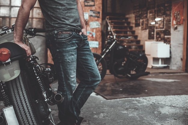 Man near his bike. confident young man keeping arms crossed and looking at camera while standing near his motorcycle garage or repair shop