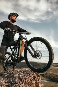 Man near mountain bicycle on boulder