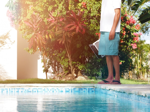 Man near a swimming pool with a laptop