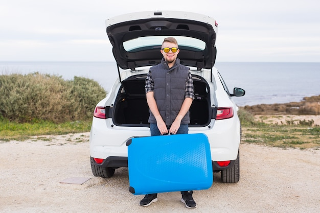 青いスーツケースを持った車の近くの男