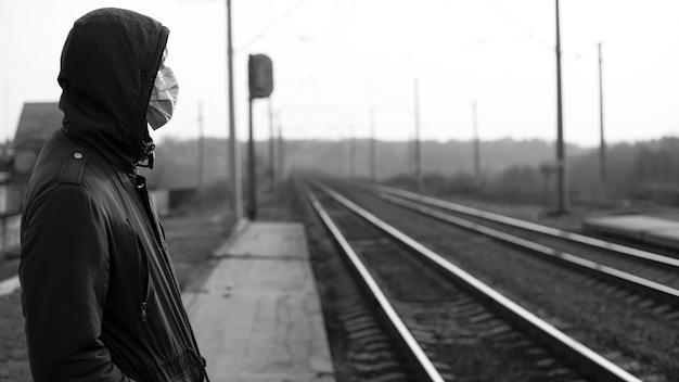 Человек у железной дороги, мировой карантин, вспышка эпидемии коронавируса.