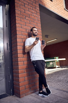 스마트 폰 및 커피 벽 근처 남자