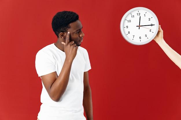 白いtシャツのトリミングされたビューで時計の横に男