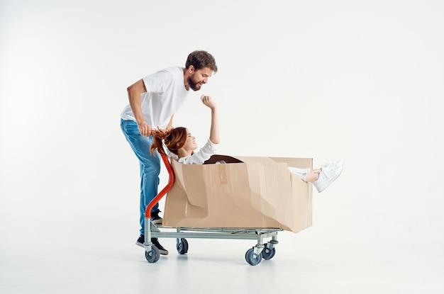 Мужчина рядом с женщиной, отправляющей транспорт в коробке, изолированный фон
