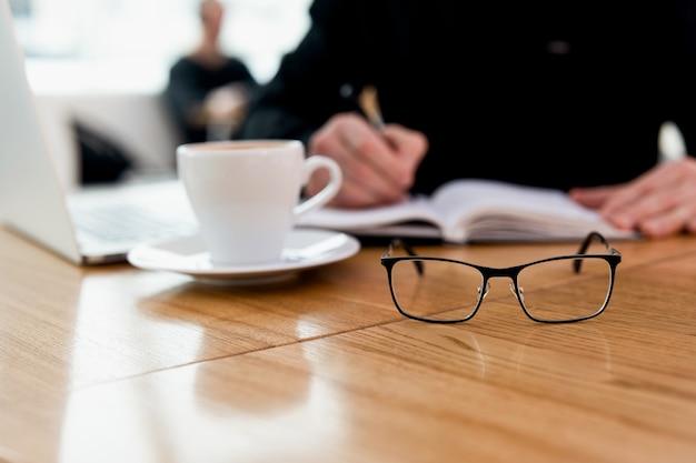 男はもう眼鏡は必要ありません!若い集中フリーランサーは黒のシャツを着て日記に出会いの日付を書き、コーヒーショップで素晴らしいカプチーノを楽しんでいます。テーブルの上のモダンなラプロップと白いマグカップ。