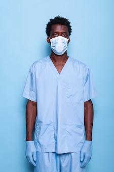 파란색 배경 위에 스튜디오에 서 있는 남자 간호사