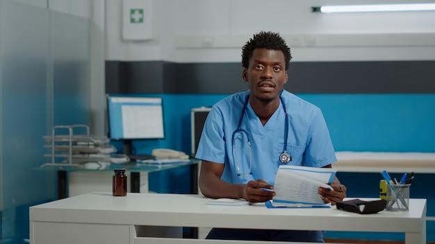 机に座ってビデオ通話技術について話している男性看護師