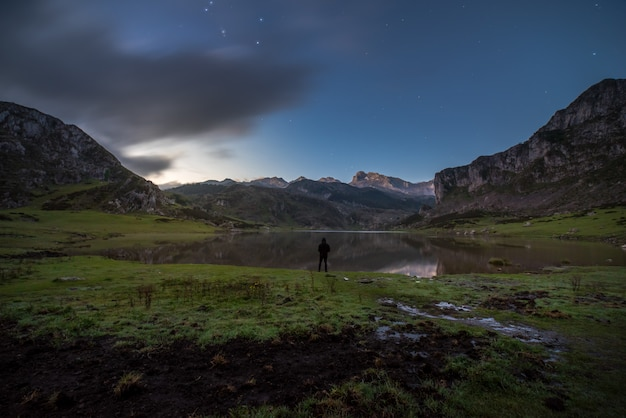 A man observes the lake of the mountains of asturias,spain
