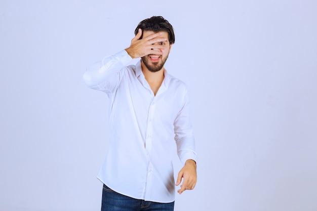 指で外を見たり、顔を隠したりする男。