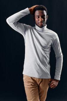 彼の頭の孤立した背景を保持している灰色のセーターでアフリカの外観の男
