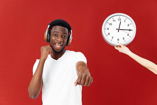 時計の横で彼の手で身振りで示すヘッドフォンでアフリカの外観の男