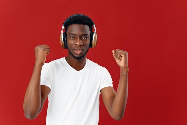 ヘッドフォンでアフリカの外観の男。音楽愛好家のライフスタイルの赤い背景。高品質の写真