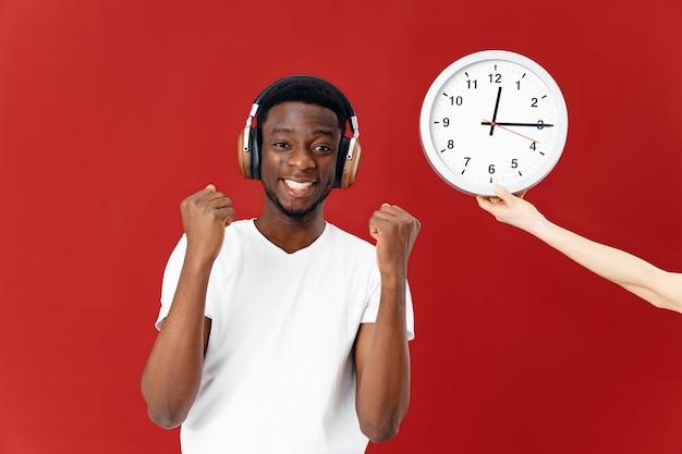 白いtシャツの時計の横にあるヘッドフォンでアフリカの外観の男
