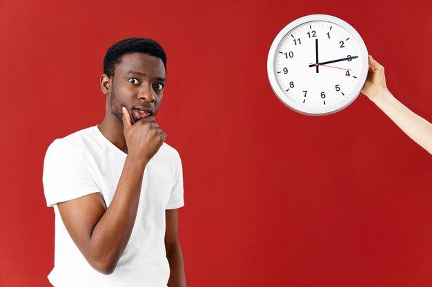 白いtシャツの時計の赤い背景のアフリカの外観の男
