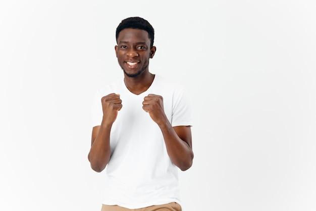 現代の手で身振りで示す白いtシャツのアフリカの外観の男