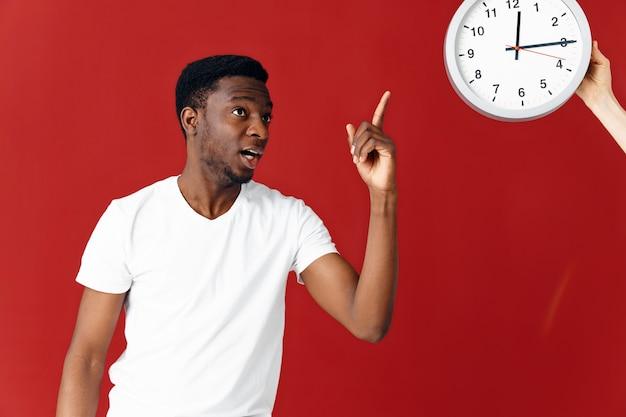 白いtシャツでアフリカの外観の男は時計スタジオで彼の指を示しています