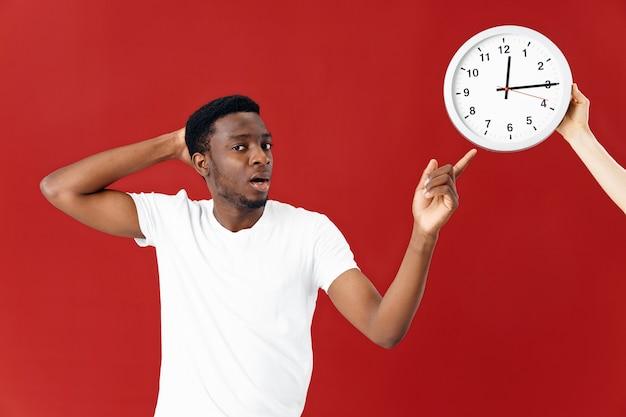アフリカの外観の男は時計の白いtシャツスタジオで感情を示しています