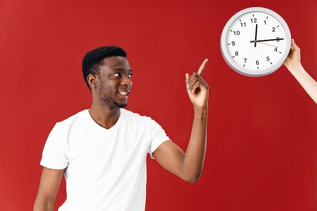 アフリカの外観の男は、時計の赤い背景で指を示しています