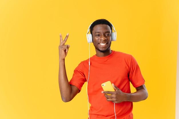 音楽ダンスを聴いているヘッドフォンでアフリカの外観の男