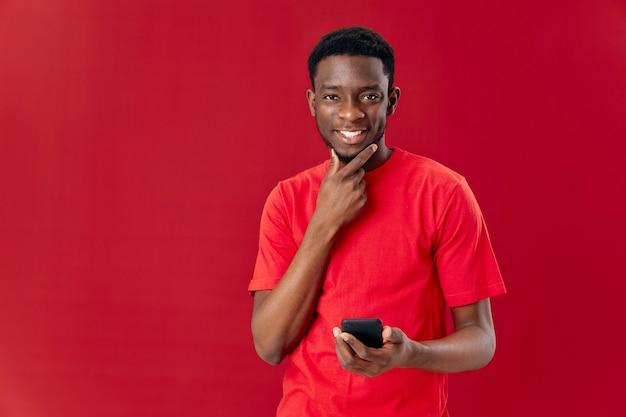 手に電話を持ったアフリカの外観の男は、分離された技術の背景を切り取ったビュー