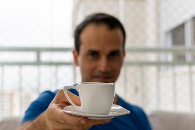 Мужчина предлагает чашку кофе с размытым