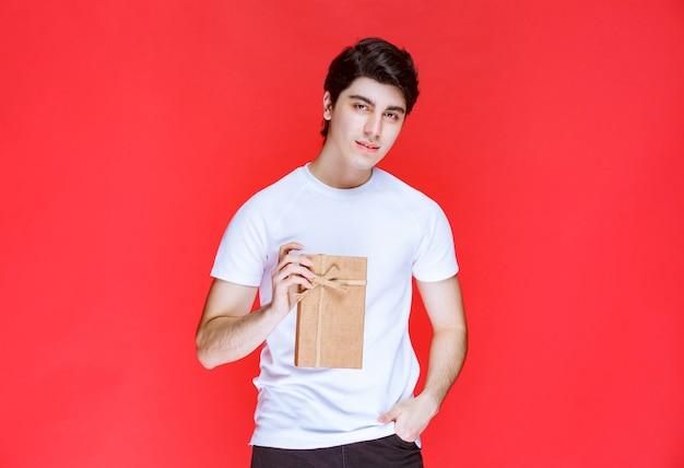 Мужчина предлагает партнеру небольшую подарочную коробку в картонной упаковке.